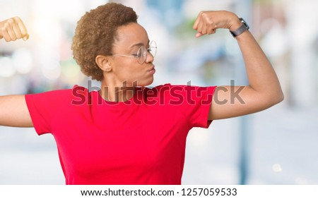 Beautiful young african american woman wearing glasses over isolated background showing arms muscles smiling proud. Fitness concept. #1257059533