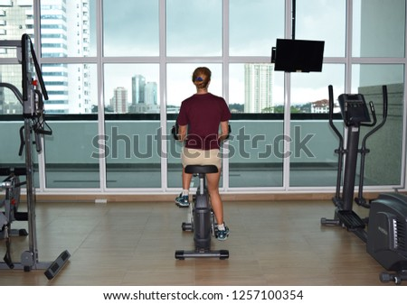 Johor Bahru Malaysia December 9, 2018: Woman is training on bicycle machine in the skyscraper gym in megapolis. #1257100354