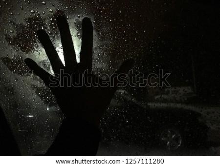 Shadow horror hand on a wet car glass window #1257111280