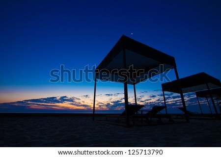 Twilight morning by the beach with beach tent and bench in silhouette #125713790