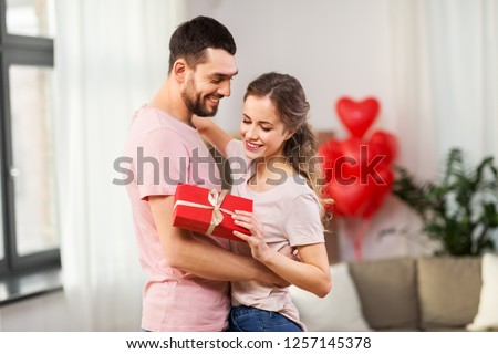 valentines day, relationships and people concept - happy couple with gift box hugging at home #1257145378