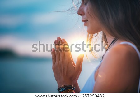 Young woman meditating with her eyes closed, practicing Yoga with hands in prayer position.   #1257250432