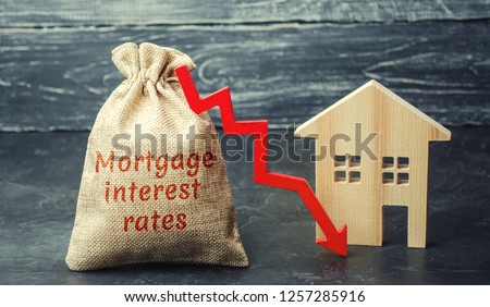 Bag with the money and the word Mortgage interest rates and arrow to down and house. Low interest in mortgages. Reducing interest payments for mortgages. The fall in housing rates on credit. Low #1257285916
