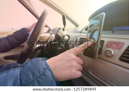 Woman using smart phone as navigation while driving the car. Risky driving behaviors concept #1257289849