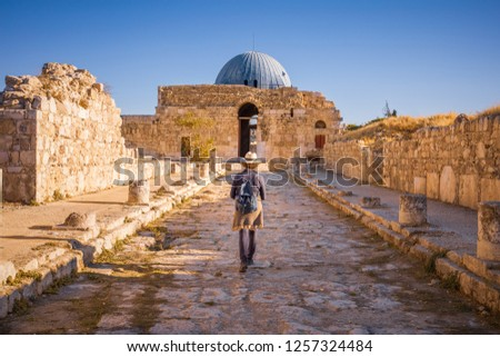 Lady walking along Colonnated Street toward the Monumental Gateway at Umayyad Palace, Amman Citadel, Amman, Jordan #1257324484