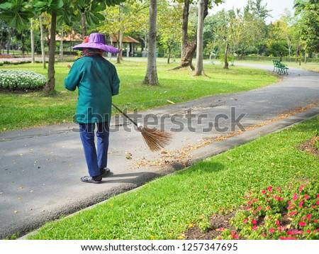 Gardener sweeping dry leaves in the park. #1257347695