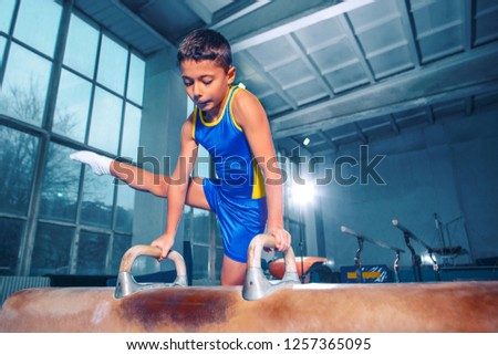 The sportsman performing difficult gymnastic exercise at gym. The sport, exercise, gymnast, health, training, athlete concept. Caucasian fit little boy #1257365095