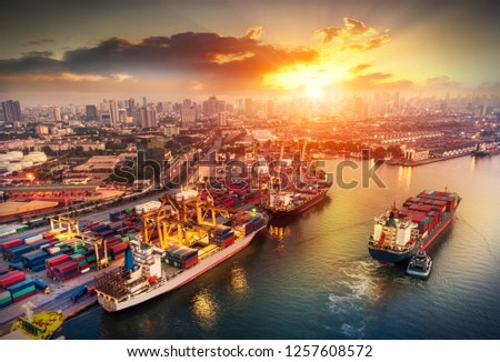 Logistics and transportation of Container Cargo ship and Cargo plane with working crane bridge in shipyard at sunrise, logistic import export and transport industry background #1257608572