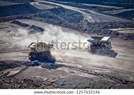 Two diesel electric trucks used in modern mines and quarries for hauling industrial quantities of ore or coal. Used when extra torque is needed for steep hills. Blackwater, Australia. Logos removed. #1257632146