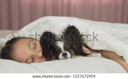 Beautiful teen girl sleeping sweetly in bed with a Papillon dog #1257672904