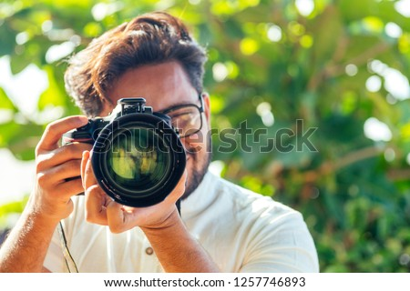 handsome and confident indian man photographer with a large professional camera taking pictures photo shooting on the beach.photo session on summer holiday on the background of green tropical trees Royalty-Free Stock Photo #1257746893