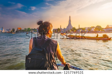 Traveler woman on boat joy view Wat Arun at sunset, Chao Phraya river, Famous water landmark travel Bangkok Thailand, tourist female on holiday vacation trips, Tourism beautiful destination place Asia #1257769531