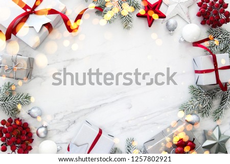 Christmas silver and red gifts and ornaments on white marble background top view. Merry Christmas greeting card, frame. Winter xmas holiday theme. Noel. Happy New Year. Flat lay #1257802921