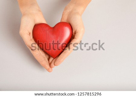 Woman holding decorative heart on light background, top view with space for text #1257815296