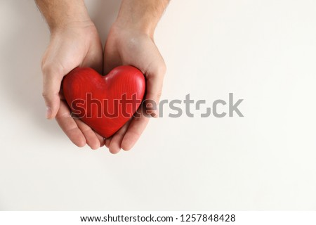 Man holding decorative heart on white background, top view with space for text #1257848428