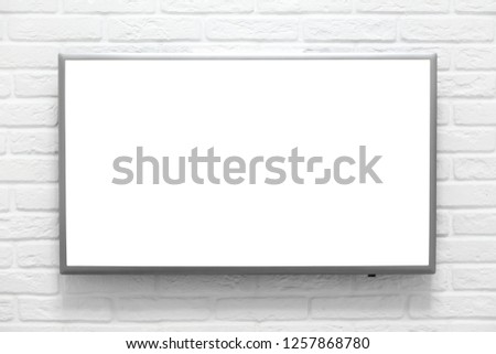 Mockup with empty TV set screen on white brick wall #1257868780