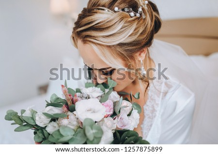 Blonde bride sits on a white bed and sniffs a bouquet. Wedding interior. Charges the bride at the hotel. Wedding photography. Portrait of a cute bride. #1257875899
