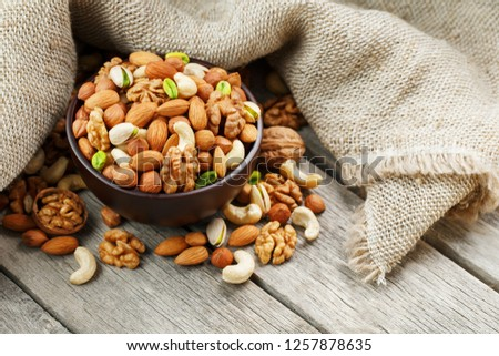 Wooden bowl with nuts on a wooden background, near a bag from burlap. Healthy food and snack, organic vegetarian food. Walnut, pistachios, almonds, hazelnuts and nuts of cashew, walnut. Top view. Vert #1257878635