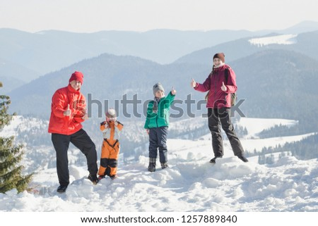 Mother, father and two sons are standing and smiling against the backdrop of snow-capped mountains. Happy family. Winter sunny day #1257889840