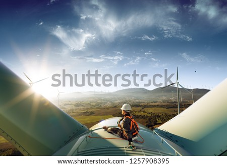 Happy engineer feel success after good work. He standing a top of windmill and looking beautiful sunset landscape Royalty-Free Stock Photo #1257908395