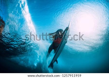 Attractive surfer woman dive underwater with under barrel wave. #1257911959