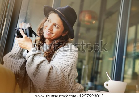 Beautiful brunette in modern cafe with vintage camera #1257993013