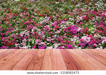 Wooden table top and pink flower background. #1258082473