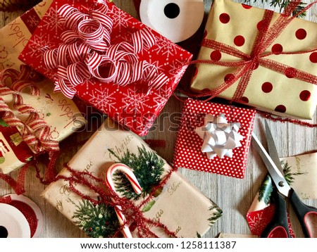 Christmas gifts with wrapping and ribbon on a rustic wooden surface #1258111387