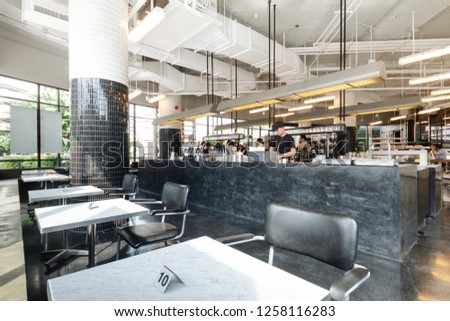 BANGKOK, THAILAND. JULY 28, 2016: Black and white industrial decorated interior design, Coffee bar black granite counter with baristas and customers in restaurant cafe.  #1258116283