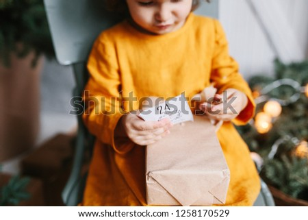 Cute curly toddler girl wearing mustard linen dress in studio near christmas tree opening christmas gift. Minimalistic stylish scandinavian christamas decoration. Advent calendar guft with number 24