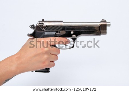 Woman holding gun in hand #1258189192