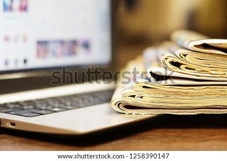 Newspapers and Laptop. Different Concepts for News - Social Network or Traditional Tabloid Journals. Data Sources - Electronic Screen of Computer or Paper Pages of Magazines, Internet or Papers Royalty-Free Stock Photo #1258390147