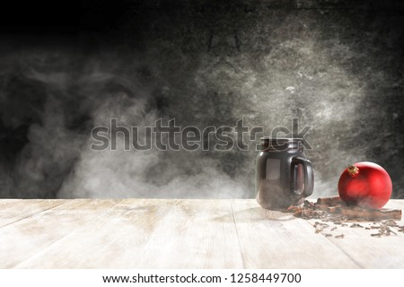 Christmas mug with free space for your decoration and dark background. Smoke decoration and mood photo style.  #1258449700