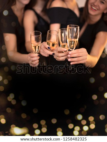 Cheers! Group of people cheering with champagne flutes with holiday lights on background with copy space. #1258482325