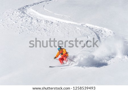 one freeride skier skiing downhill trough deep fresh powder #1258539493