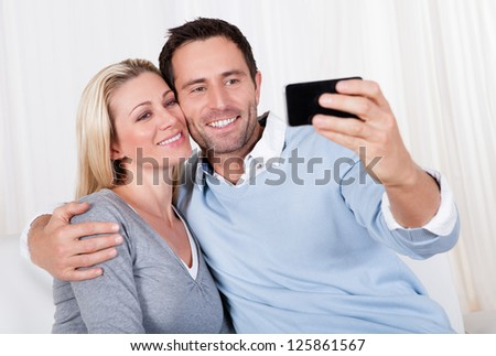 Beautiful smiling young couple photographing themselves on a mobile or smartphone posing close together with his arm around her #125861567