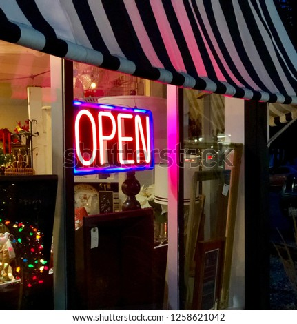 Close up of neon open sign on the exterior of a small business feature Christmas holiday items and a black and white awning