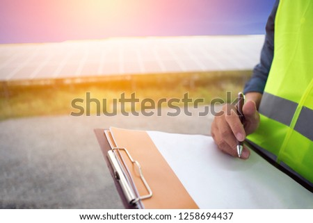 Man hand holding pen writing notes. There is a solar panel in the sun.