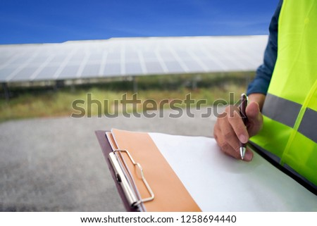 Man hand holding pen writing notes. The backdrop is a solar panel.