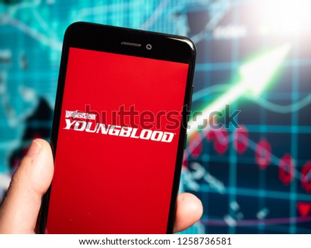 Murcia, Spain; Dic 14, 2018: Wolfenstein Youngblood red logo in phone with earnings graphic on background. Wolfenstein Youngblood is an action-adventure first-person shooter video game #1258736581