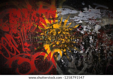 Yezidi Flag SVG flag painted on dirty street wall with graffiti texture background. National political symbol street art. #1258791547
