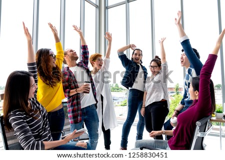 Young multiethnic diverse creative asian group huddle and high five hands together in office workshop with success or empower expression in teamwork. Young asian marketing team with copy space. #1258830451