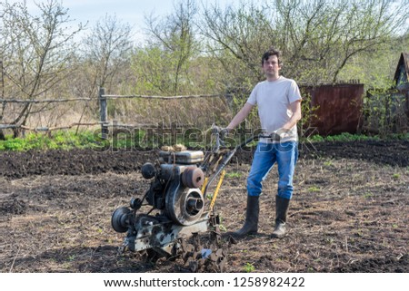 Man with cultivator ploughs ground. Land cultivation, soil tillage. Spring work in the garden. Gardening concept #1258982422