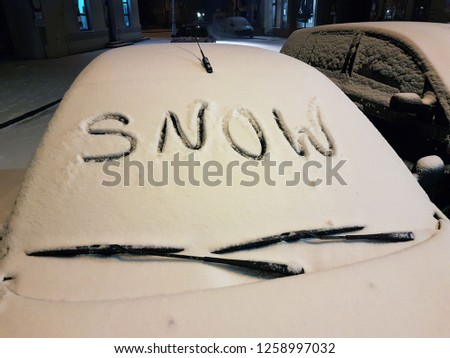 "The windshield of a passenger car covered with snow, on which the word ""snow"" was written. A winter autocar parked in the city in the evening. Weather difficulties for drivers and transport. Cleaning  #1258997032"