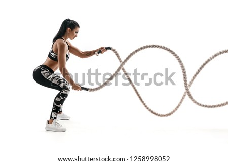 Strong muscular woman working out with battle ropes. Photo of attractive woman in fashionable sportswear isolated on white background. Strength and motivation. Side view. #1258998052