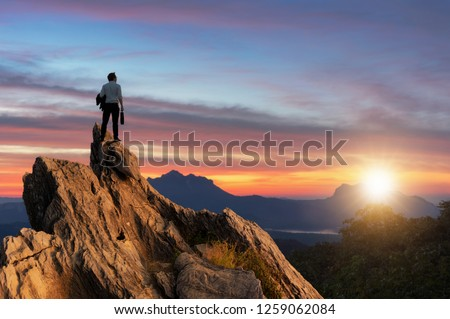 Concept vision, Young businessman wearing comfortable casual suit jacket standing holding business bag on top of peak mountain and looking forwards, success, competition and leader concept. #1259062084