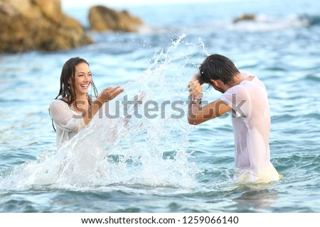 Spontaneous couple joking throwing water bathing in the sea on the beach Royalty-Free Stock Photo #1259066140