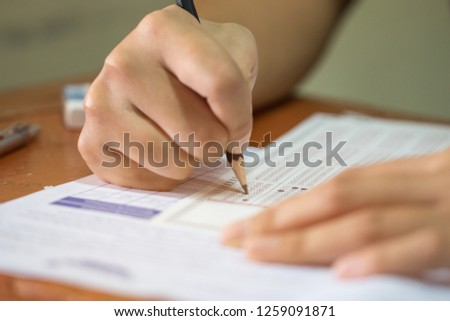 School Students hands taking exams, writing examination holding pencil on optical form of standardized test with answers sheet doing final exam in classroom. Education assessment Concept. Soft focus #1259091871