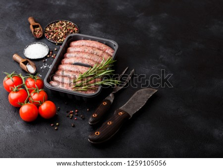 Raw beef and pork sausage in plastic tray with vintage knife and fork on black background.Salt and pepper with tomatoes #1259105056