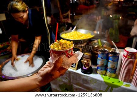 KANCHANABURI,THAILAND-DECEMBER5,2018.Corn boil, stir butter and sugar the delicious taste. Sales in River Kwai Bridge Light&sound Week.on december 5,2018 in Kanchanaburi,Thailand #1259136808